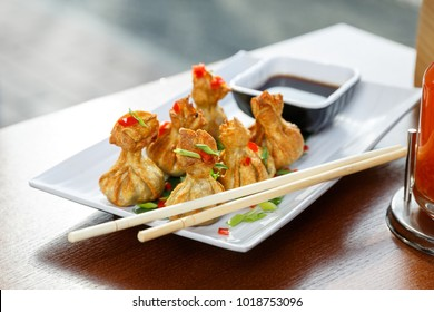 Portion of six fried wontons on a plate with sticks, standing on a table