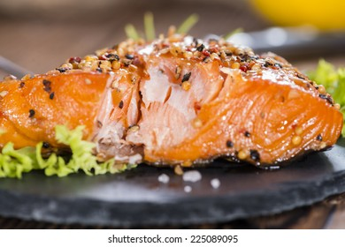 Portion of Smoked Salmon marinated with fresh herbs and spices on wooden background