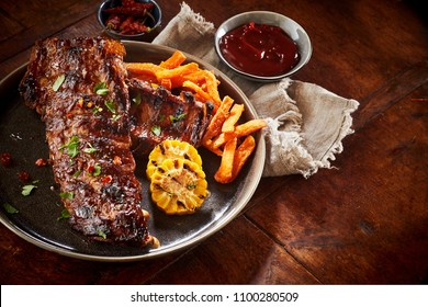 Portion of spicy barbecued spare ribs with grilled vegetables and potato chips served with a side dish of chili dip on a rustic wood table with copy space