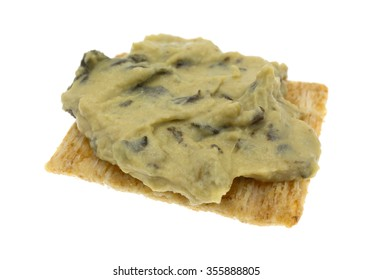 A portion of spinach hommus on a whole grain cracker isolated on a white background.
