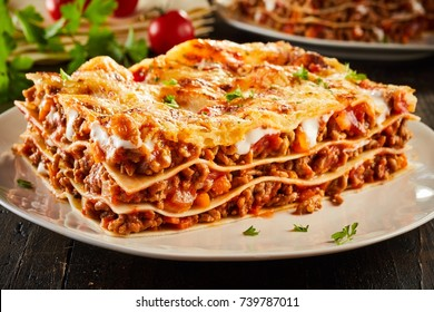 Portion of succulent ground beef lasagne topped with melted cheese and garnished with fresh parsley served on a plate in a close up view for a menu