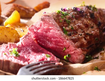 Portion of succulent rare roast beef carved for dinner with a close up view of the texture of the healthy lean red meat