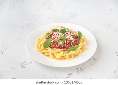 Portion of tagliatelle with bolognese sauce on the table