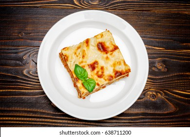 Portion of tasty lasagna on wooden backgound
