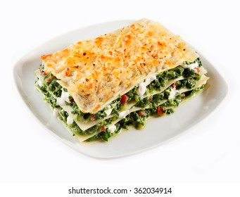 Portion of traditional Italian lasagne with spinach and mozzarella cheese served on a square plate isolated on white, high angle view
