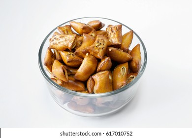 A portion of unsalted peanut butter pretzels in glass bowl on white background
