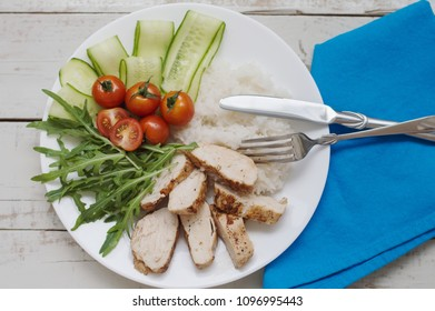 Portion of white rice with chicken breast, arugula leaves, red cherry tomatoes and cucumber served on white plate with fork, knite and blue napkin on wooden table. Meat and fresh vegetable salad