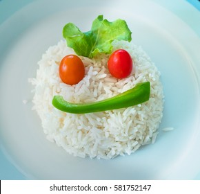 A portion of white rice on a plate shaped as a face using a slice of green bell pepper, two cherry tomatoes and a salad leaf.