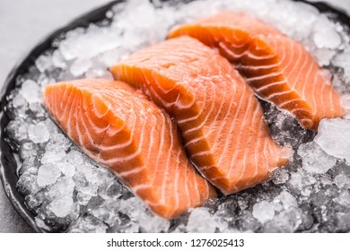 Portioned raw salmon fillets in ice on plate - Close-up.