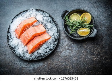 Portioned raw salmon fillets in ice on plate with lemon and rosemary.