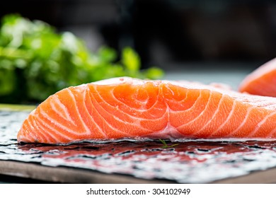 portions of fresh gourmet uncooked salmon fillet on black background
