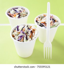 Portions of low-caloric vegetable coleslaw salad in a paper cups on braght green background. Concept for healthy eating. Selective focus.