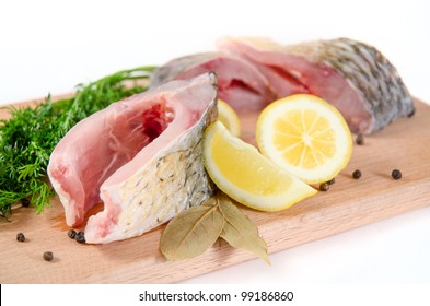 Portions of raw carp fish on a cutting board
