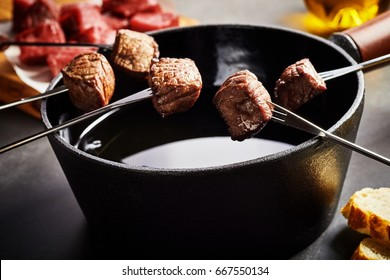 Portions of tender beef cooked in a fondue pot displayed on forks above the oil with ingredients in the background