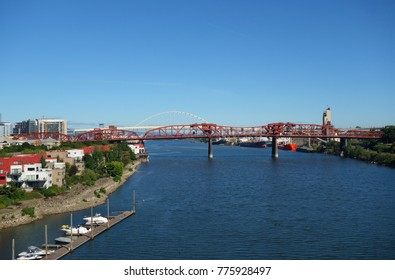 PORTLAND, OR -21 JUL 2017- Day view of the Willamette River and the red steel Broadway Bridge in Portland, Oregon.