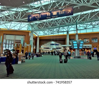 PORTLAND, OR - APRIL 14, 2016: Passengers traverse through Portland Int'l Airport, PDX, a large hub in the Pacific Northwest region of the United States. PDX recently updated its iconic green carpet.