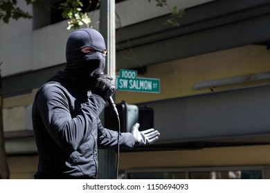 Portland, OR – August 4, 2018: An antifascist protester in black bloc garb starts a dance party in downtown Portland.