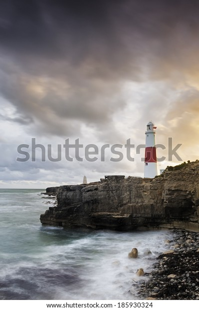 Portland Bill Lighthouse stands sentinel on the rugged south England coast as the suns last rays illuminate the impressive structure.