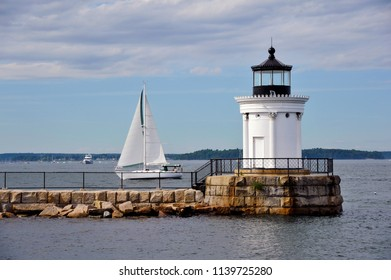 Portland Breakwater lighthouse, also referred to as Bug light, guides a sailboat into Portland Harbor n a summer day in Maine.