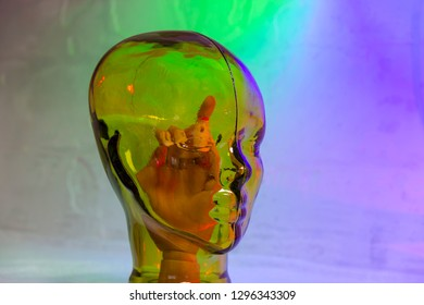 Portland, Dorset, England - 27 January 2019: A glass head with a manikin hand inside as a meaphore for thought control or manipulation.