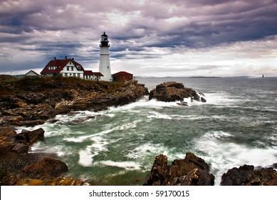 Portland Head Lighthouse sits on the edge of the Atlantic Ocean while the waves crash on the rocky coast