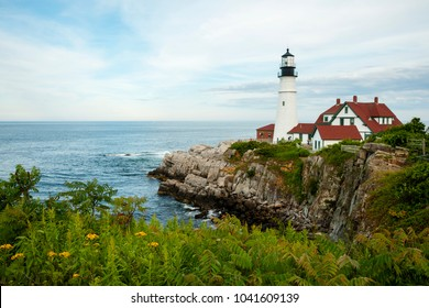 Portland Head lighthouse sits over rocky cliffs at low tide with wildflowers blooming on a warm summer day. This iconic beacon is the oldest in Maine.