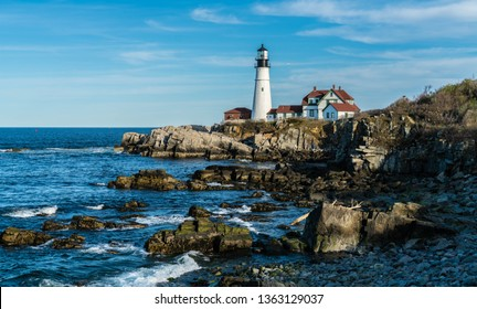 Portland Headlight standing tall off the coast of Cape Elizabeth, Maine. An historic light house, it is the oldest light house in the state of Maine, standing at the edge of jagged cliffs.