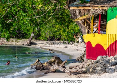 Portland, Jamaica - May 11 2019: People swim in tropical island beach setting with white sand & lush trees. Rasta color Jamaican vendor shop of board, wood, bamboo, zinc & thatch roof built on rocks.