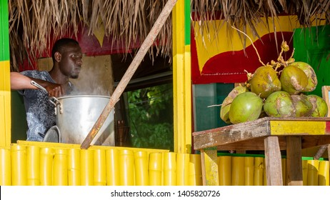 Portland, Jamaica - May 11 2019: Young black Jamaican millennial man stirring big pot of soup cooking in food vendor shop on beach painted in rasta colors. Ripe tropical jelly coconut fruits on table.
