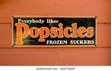 Portland, Main, USA - 31st August 2014: Old tin advertising panel for Popsicles, with slogan Everybody likes Popsicles Frozen Suckers.