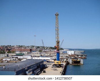 Portland, Maine - May 26, 2010: Large Crane at Maine Port Authority Terminal and Portland Skyline.  Taken from the Casco bridge.