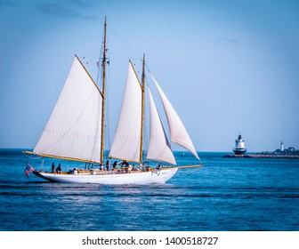 Portland, Maine, USA - June 08, 2018: Tourists on a schooner tour sailing along lighthouses in Portland Maine.