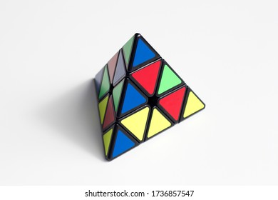 Portland, OR, USA - Apr 19, 2020: Scrambled Pyraminx isolated on white. The Pyraminx is a regular tetrahedron puzzle in the style of Rubik's Cube, and was introduced by Tomy Toys of Japan in 1981.