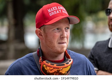 Portland, OR, USA - August 17 2019: Proud Boys and other far-right groups are met by counter-demonstrators. A red-haired man in a MAGA hat and an uneasy expression had worn ski goggles for protection.