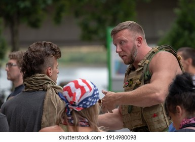 Portland, OR, USA - August 17 2019: Far-right groups are met by counter-demonstrators. A man in tactical gear displaying Proud Boys and Three Percenter patches talks with people in the crowd.