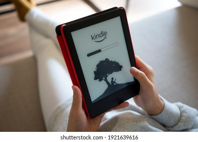 Portland, OR, USA - Feb 20, 2021: A girl opens her kindle to read ebooks at home.