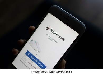 Portland, OR, USA - Jan 19, 2021: A woman opens the Poshmark app on her iPhone. Poshmark is a social commerce marketplace where people can buy or sell new or used clothing, shoes, and accessories.