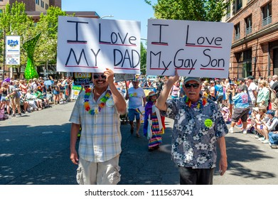 Portland OR, USA - June 17, 2018: A father and a son marching together during the 2018 Pride Parade through the streets of downtown Portland.