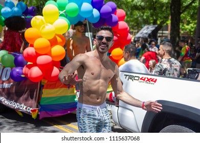 Portland OR, USA - June 17, 2018: A man dances along side one of the many floats during the 2018 Pride Parade through the streets of downtown Portland.