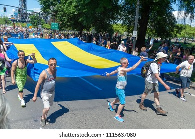 Portland OR, USA - June 17, 2018: A group carries a huge equality flag during the 2018 Pride Parade through the streets of downtown Portland.