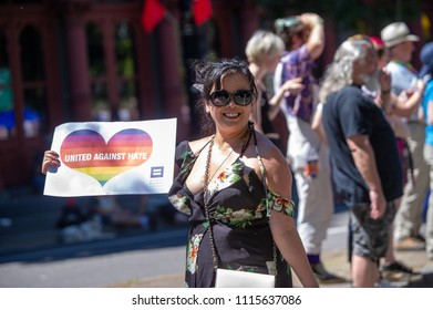 "Portland OR, USA - June 17, 2018: A woman holds a sign with ""united against hate"" written during the 2018 Pride Parade through the streets of downtown Portland."