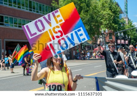 "Portland OR, USA - June 17, 2018: A woman holds a sign expressing that ""Love is Love"" during annual Pride Parade through the streets of downtown Portland."