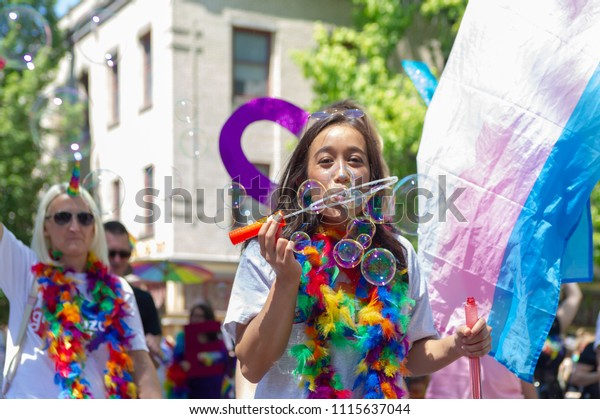 Portland OR, USA - June 17, 2018: A woman makes bubbles during the 2018 Pride Parade through the streets of downtown Portland.
