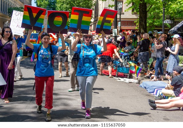 Portland OR, USA - June 17, 2018: Two women walk with a clear message to vote come next elections during the 2018 Pride Parade through the streets of downtown Portland.