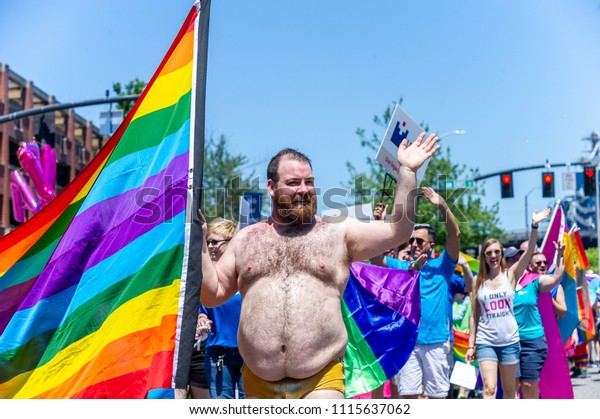 Portland OR, USA - June 17, 2018: A half naked man parades with the rainbow flag during the 2018 Pride Parade through the streets of downtown Portland.