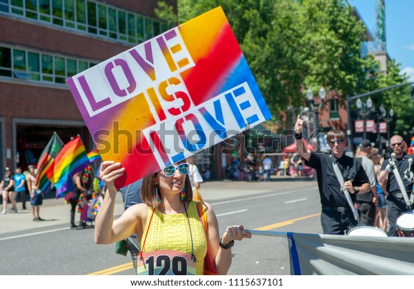 """Portland OR, USA - June 17, 2018: A woman holds a sign expressing that """"Love is Love"""" during annual Pride Parade through the streets of downtown Portland."""
