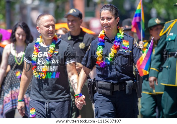 Portland OR, USA - June 17, 2018: A LGBT officer marches with her partner during the 2018 Pride Parade through the streets of downtown Portland.