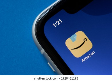 Portland, OR, USA - Mar 4, 2021: The new Amazon app icon is seen on an iPhone, showing a blue packing tape above Amazon's signature smile-shaped arrow.