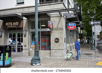 Portland, OR, USA - May 15, 2020: A masked elderly walks past a RITE AID pharmacy location in the Pearl District of Portland, Oregon. Rite Aid Corporation is a drugstore chain in the United States.
