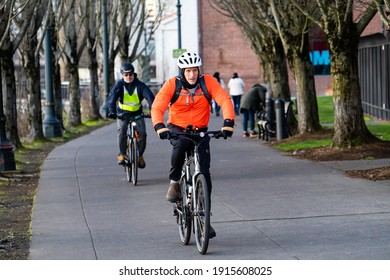Portland, Oregon - 2-11-2021: Two men riding a bicycles on the pedestrian bicycle path on the east shore of the Willamette River in Portland Oregon